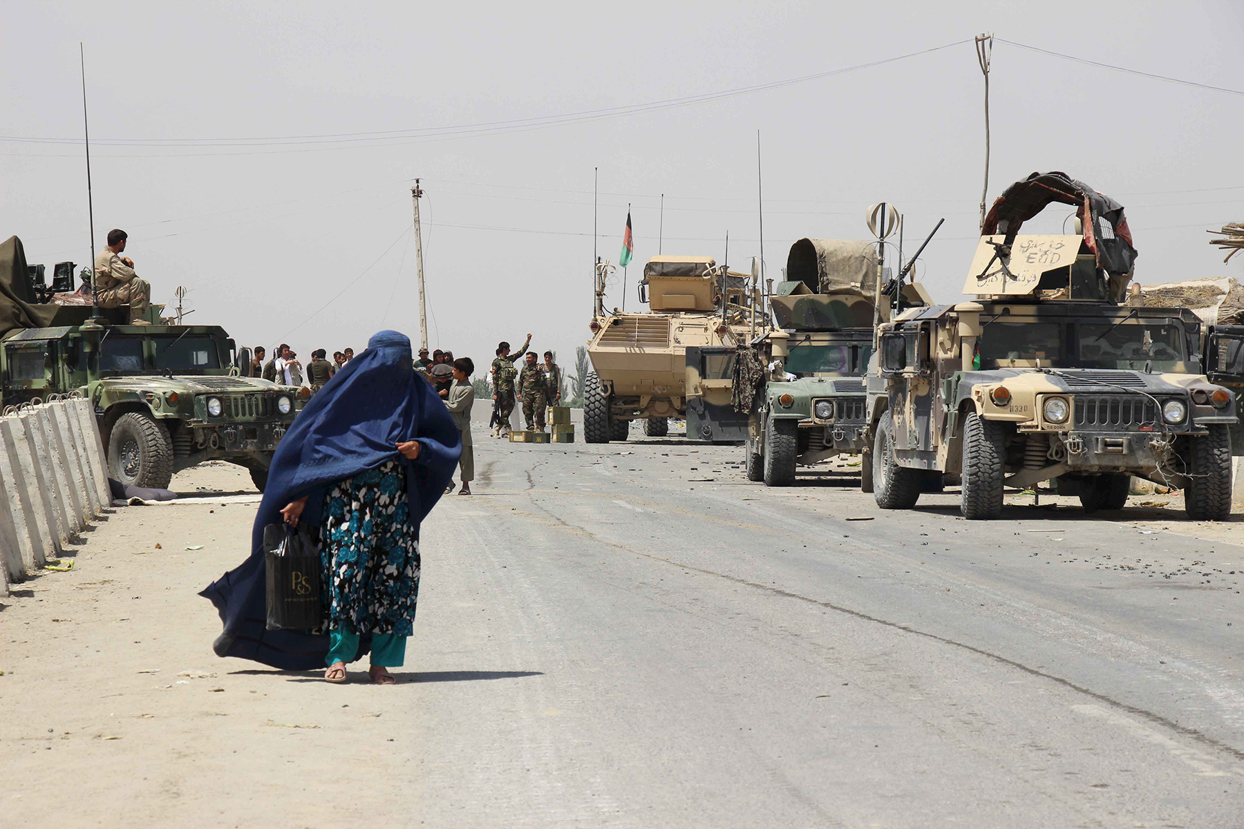 Woman in burqa walking next to tanks.