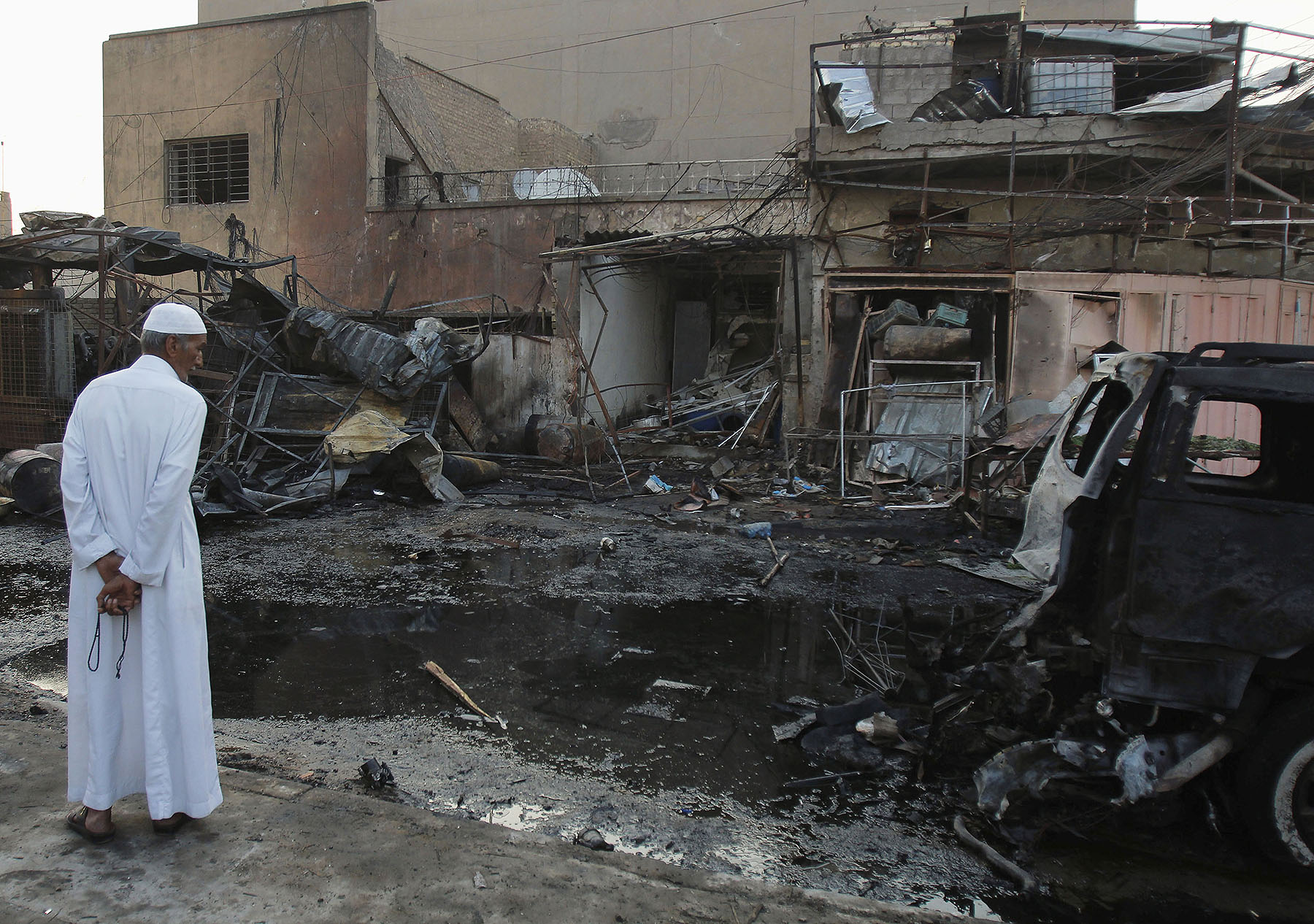 A man inspects the site a day after a bomb attack in Baghdad.