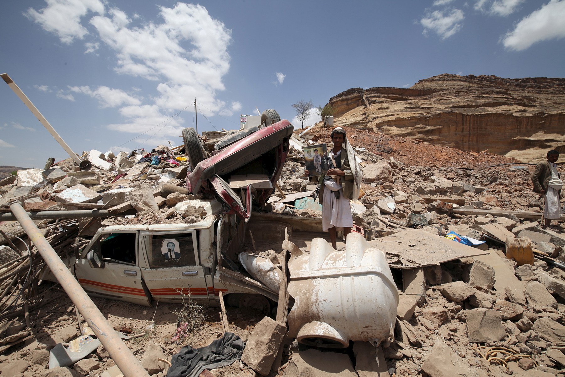 A Houthi militant stands amidst debris from a house.