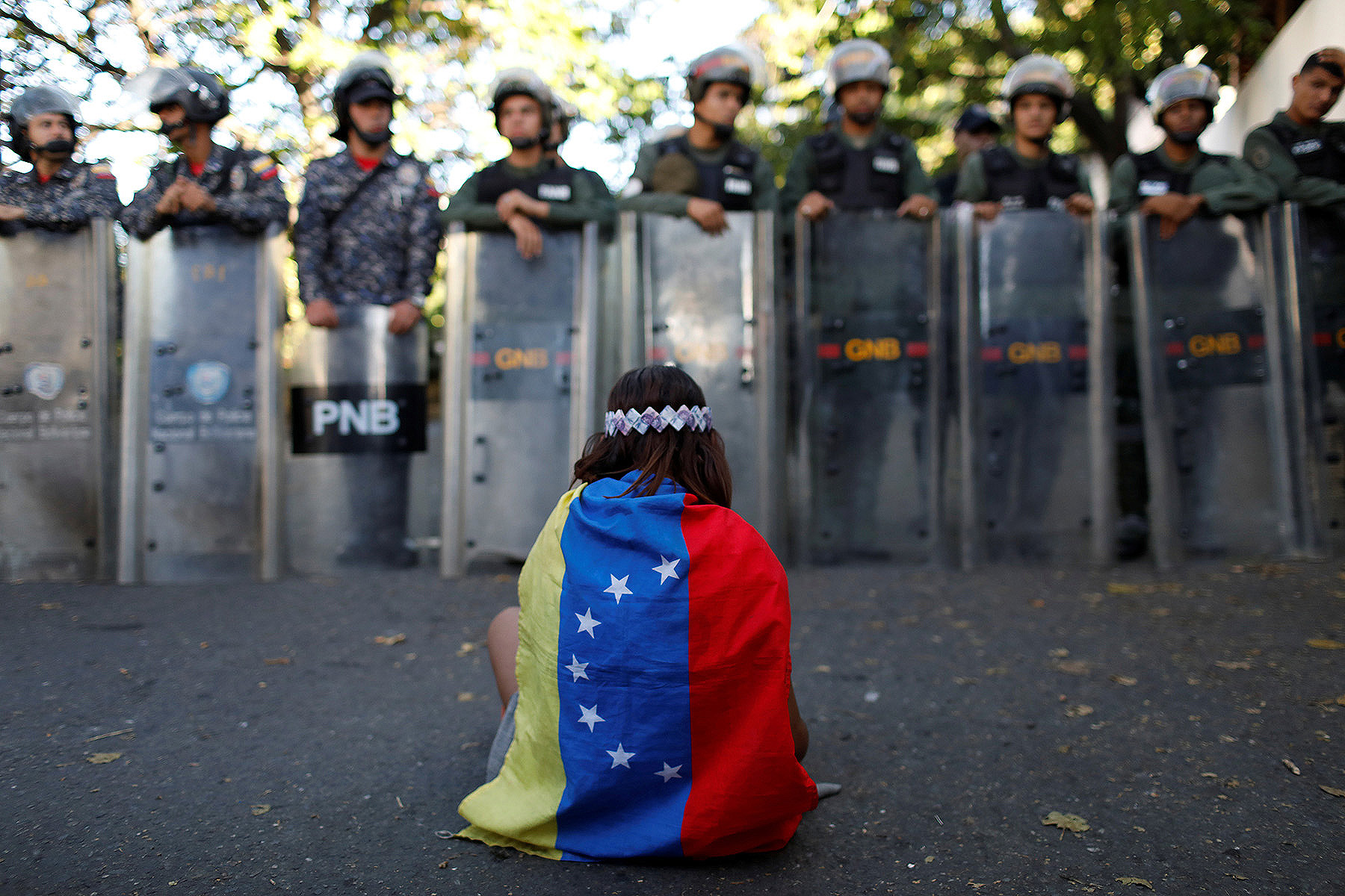 Girl wearing Venezuelan flag sits in front of security forces.